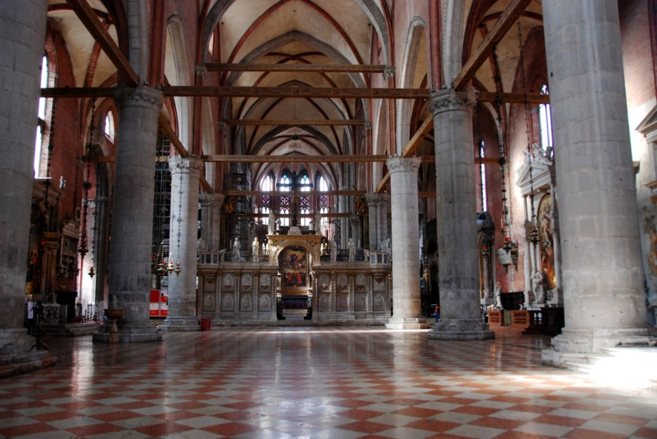 View of the nave of Santa Maria Gloriosa dei Frari, looking through the gate of the Schola Cantorum toward Titian's sumptuous Assumption of the Virgin over the high altar. Note that no tiles in the floor have been left missing for the sake of historical meaning.