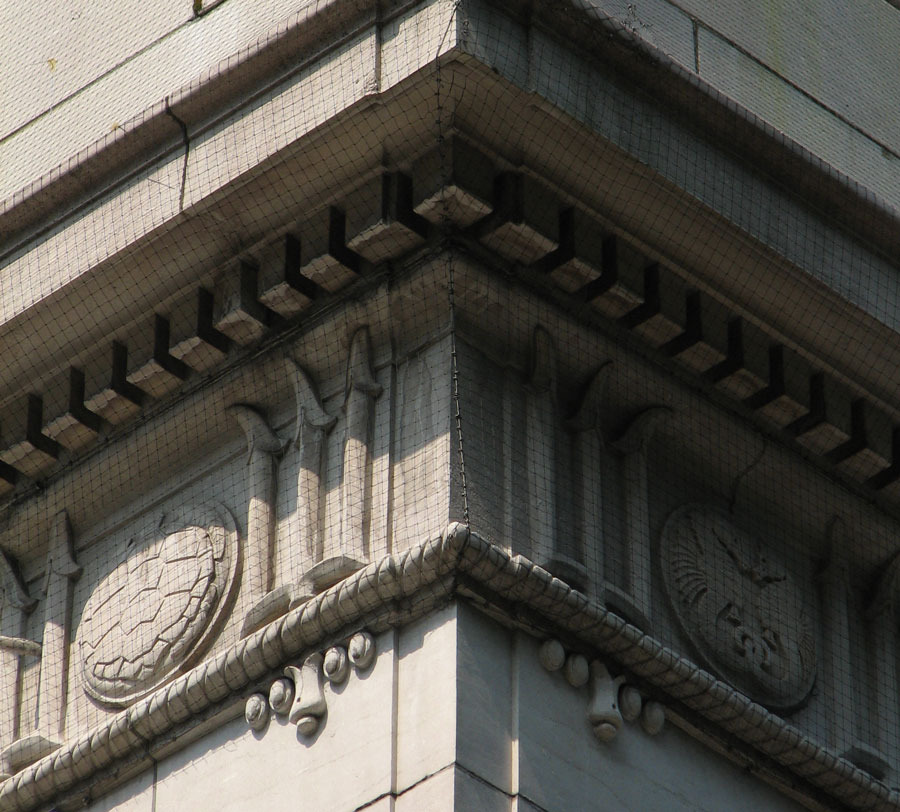 Tridents and sea creatures are a clever variation on the triglyphs and paterae we expect to find in a Doric entablature.